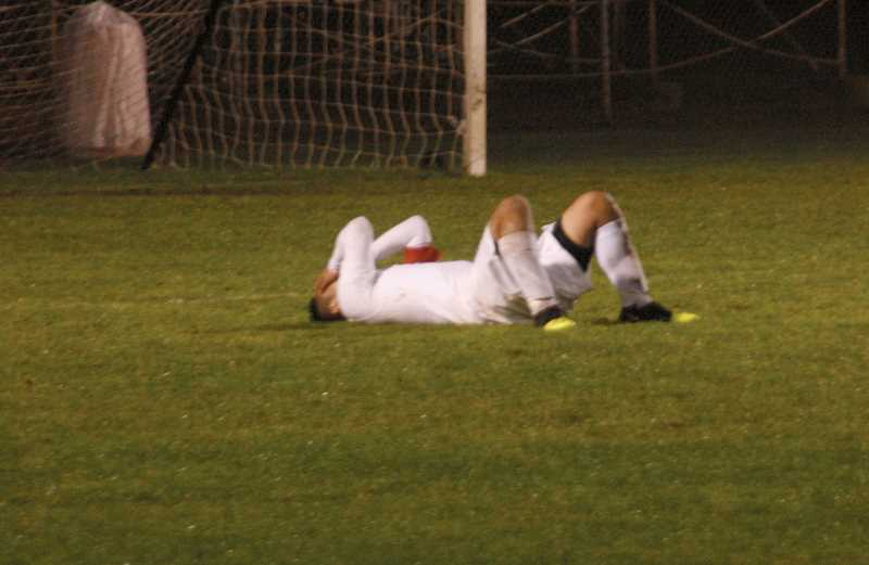 by: PHIL HAWKINS - Woodburn's Dago Diaz collapses to the ground following the Bulldogs' 3-1 overtime loss to Hood River Valley in the semifinals of the OSAA 5A boys soccer playoffs.