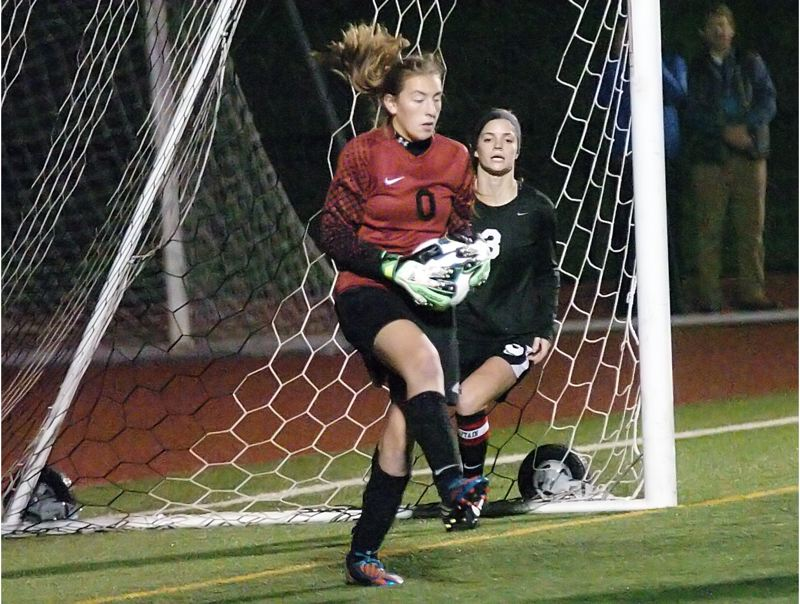 by: DAN BROOD - I GOT IT -- Tualatin sophomore goalkeeper Emily Leonard, with senior Jill Farley to her left, pulls down the ball after making a key save on a free kick attempt late in Tuesday's state playoff semifinal contest.
