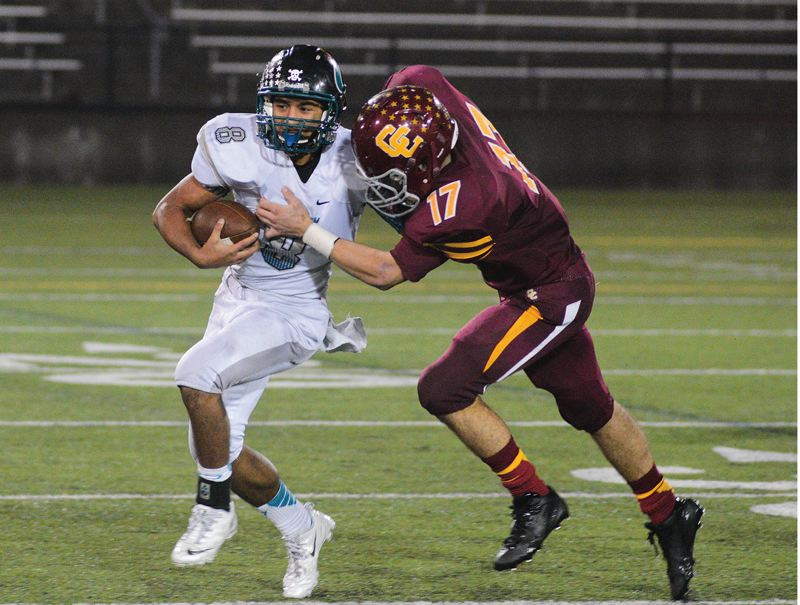 by: HILLSBORO TRIBUNE PHOTO: CHASE ALLGOOD - Century quarterback Marcos Hernandez is dragged down by Central Catholic's Ronnie Rust during last Friday's state playoff game.