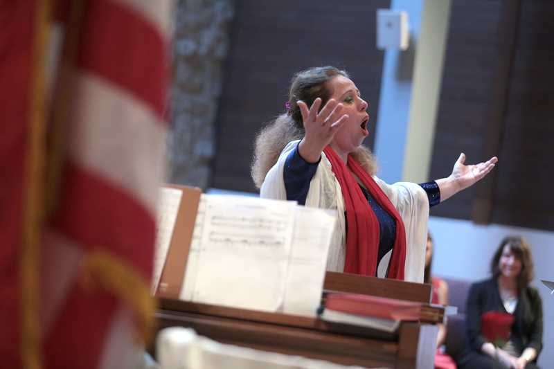 by: TIMES PHOTO: JONATHAN HOUSE - Anna Kazakova sings 'God Bless America' during the Beaverton American Legion Post 124's Veterans Day program.