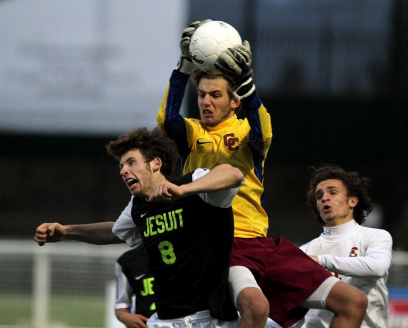 Central Catholic goalkeeper Tristan Cooper goes high to deny Henry Rocker of Jesuit.