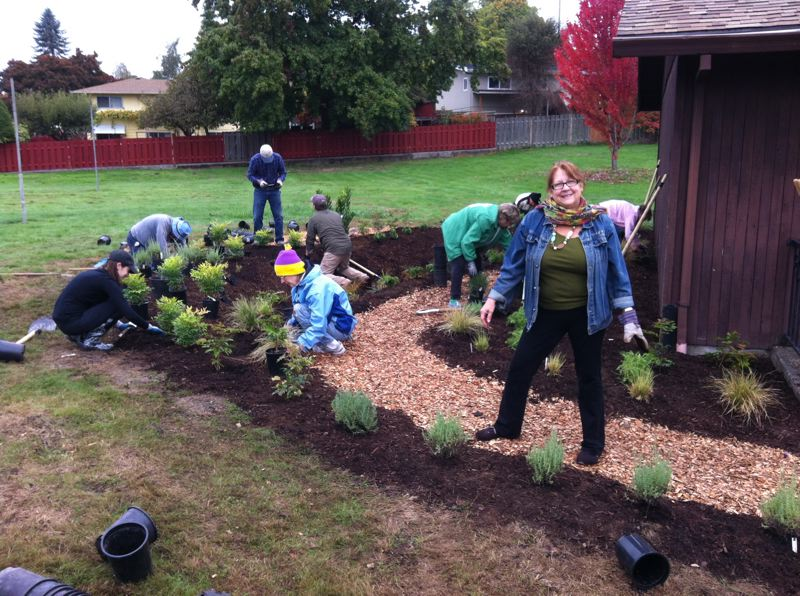 by: PHOTO COURTESY: LORI PROUTY - The Rev. Denise Andersen, Clackamas UCC pastor (standing), and Jean Hererra (kneeling in pink and yellow hat) also of CUCC, who spearheaded the rain garden, join community and church volunteers in completing the project.