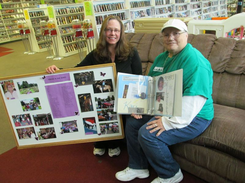 by: PHOTO BY ELLEN SPITALERI - Pam Bisson, left, and Carolyn Hammett display a poster with photos of WOW events, and a scrapbook depicting past WOW members.