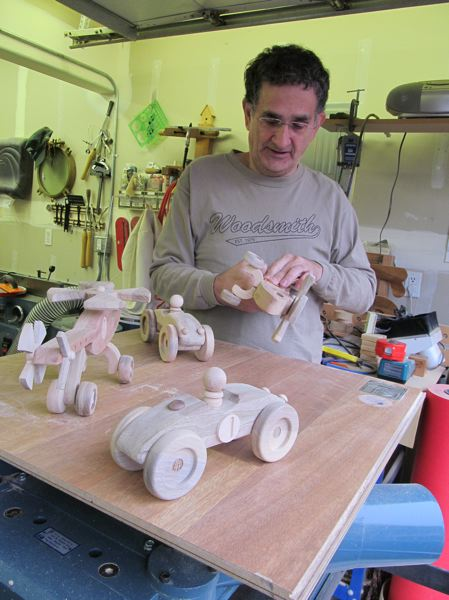 by: ELLEN SPITALERI - Marc Staino sands one of his wooden toys in his Happy Valley workshop.