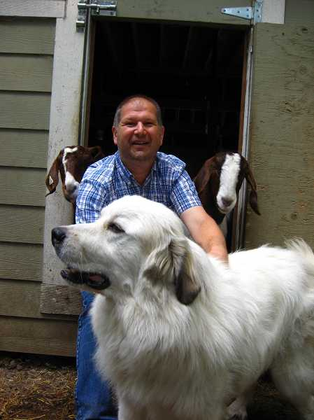 by: RAY PITZ - Jos Jacobs, a landowner along Morgan Road whose property is near the border of the proposed quarry property, poses earlier with his dog and a couple of goats. Jacobs said he'll wait for the county's written decision to see if he and others will appeal the decision.