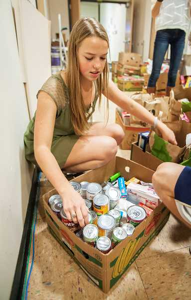 by: PAMPLIN MEDIA GROUP: JOSH KULLA - WLHS senior Madi Mills tallies canned food donations.