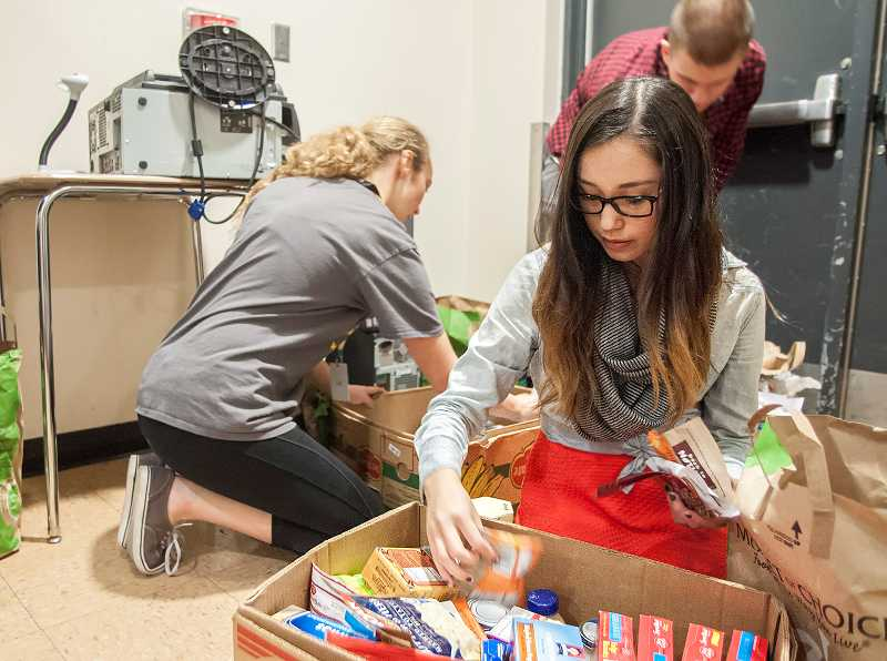 by: PAMPLIN MEDIA GROUP: JOSH KULLA - Ciara Ward, a senior at West Linn High School, sorts through nonperishable food donations during the schools annual canned food drive.