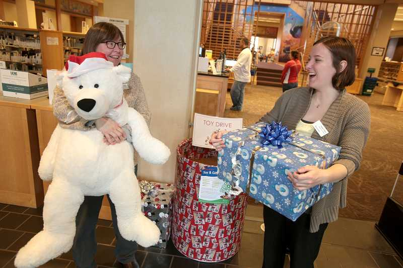 by: TIMES PHOTO: JONATHAN HOUSE - Megan Cohen, right, coordinator of city's Neighborhood Program, and Beaverton City Library circulation manager Melissa Little talk about the benefits of the food and toy drive being spearheaded by the city and Tualatin Valley Gleaners.