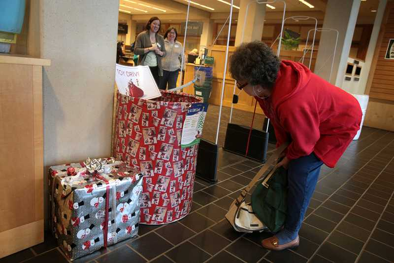 by: TIMES PHOTO: JONATHAN HOUSE - A Beaverton library patron checks out the new holiday donation container for the city of Beaverton and Tualatin Valley Gleaners' toy and gift card drive.