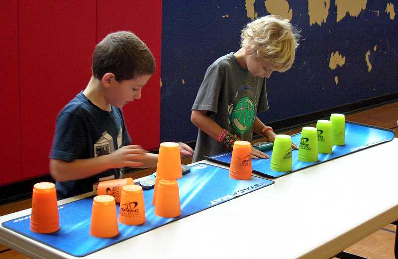 by: REVIEW PHOTO: JILLIAN DALEY - Second-grader Lucas Anderson, left, and second-grader Cohen Ross focus on their cup-stacking time.