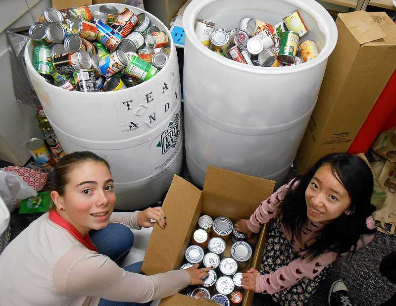 by: REVIEW PHOTO: JILLIAN DALEY - Lakeridge Junior High School eighth-grader Isabella Hoffman, left, and eighth-grader Maggie Wu box up donations during a food drive at their school.