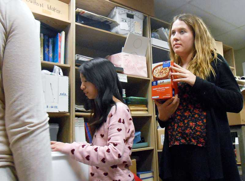 by: REVIEW PHOTO: JILLIAN DALEY - Lakeridge Junior High School food drive organizers asked donors to give healthy foods such as oatmeal, and seventh-grader Helene Stockton holds up an example of a nutritious contribution.