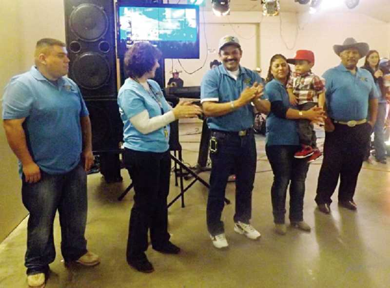 by: SUBMITTED PHOTO - Officers for Comunidad Latina en Accion, Baldemar Lopez, Minda Morton, Israel and Blanca Reynoso, and Guadalupe Estrada (left to right) are introduced and hand out prizes at the dance, which was held for all ages at the fairgrounds.