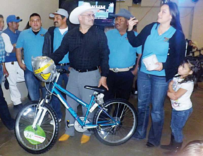 by: SUBMITTED PHOTO - Erin Tofte presents a bicycle to Abraham Torres.