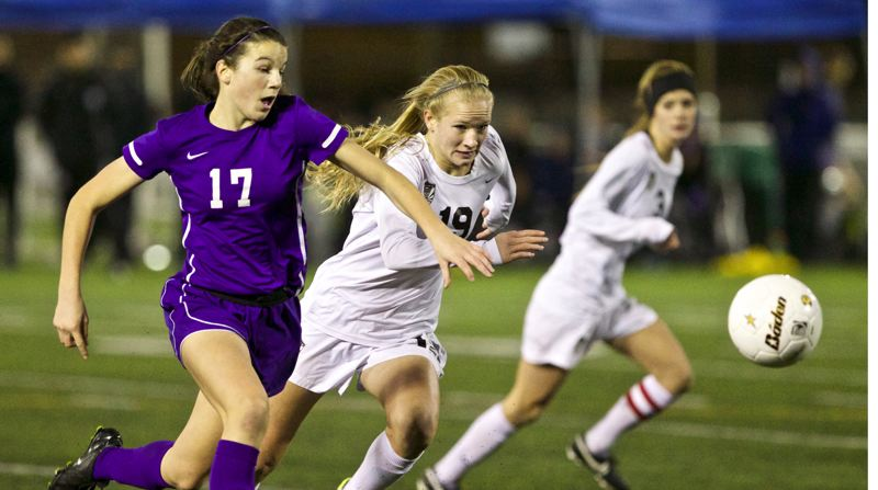 by: TIMES PHOTO: JAIME VALDEZ - Sunset Apollos midfielder Rose Pflug (17) and Tualatin Timberwolves Anna Verloo (19) chase the ball in the 6A state girls soccer championship at Hillsboro Stadium.