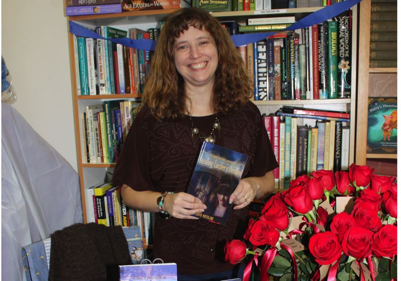 by: HILLSBORO TRIBUNE PHOTO: DOUG BURKHARDT - Tonya Macalino poses with her latest book, Stealing Lucifers Dreams, during a book release party at Jacobsens Books last Friday.