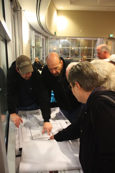 by: HILLSBORO TRIBUNE PHOTOS: DOUG BURKHARDT - Citizens at last weeks public hearing on a proposed WalMart development look at a presentation and crowd around maps and charts describing the plan. About 100 people turned out for the Nov. 13 hearing at the Hillsboro Civic Center.