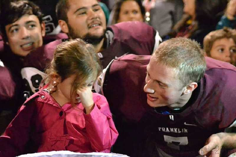by: SUBMITTED PHOTO - Aidan Marcum, a Franklin High School quaterback who is Mya's cousin and the person who arranged for his team to wear yellow socks in honor of her, talks to his young cousin during the October game.