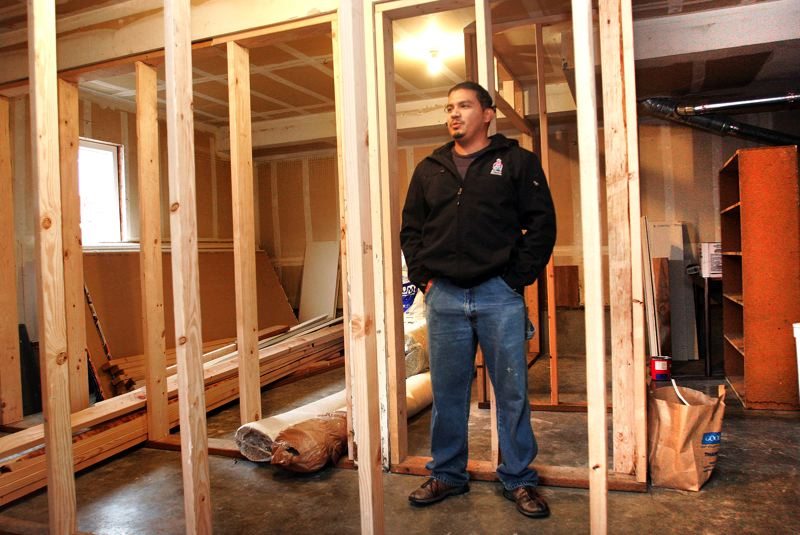 by: OUTLOOK PHOTO: JIM CLARK - Anwar Beisa, owner of Beisas Legacy Construction, stands in soon-to-be basement rooms at an Oxford house in Gresham.