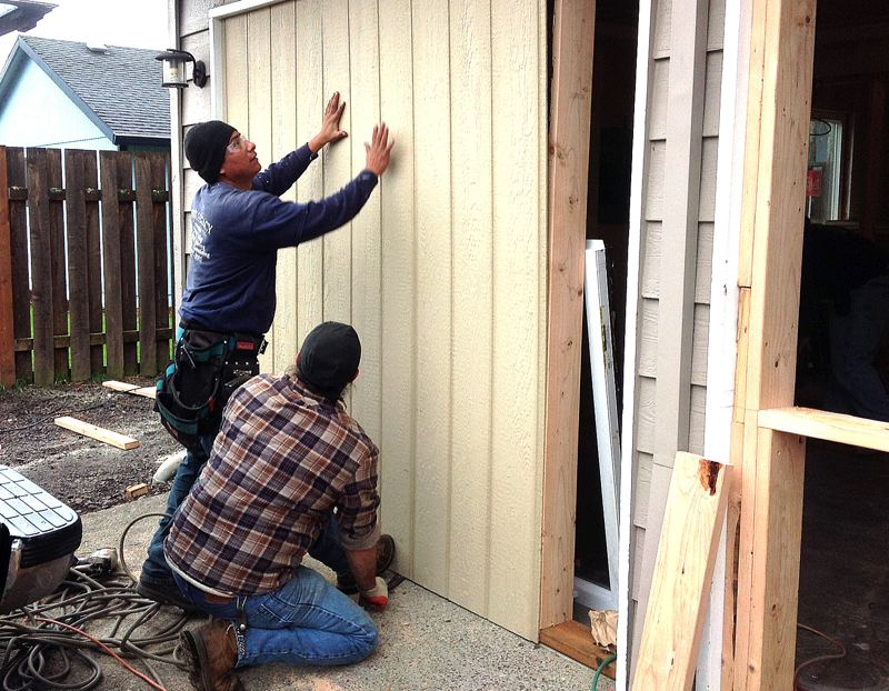 by: OUTLOOK PHOTO: JIM CLARK - Beisas Legacy workers convert the garage of an Oxford House into bedrooms for women in recovery.