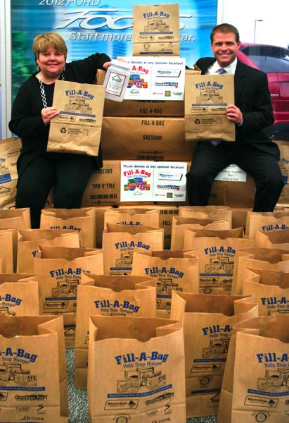 Photo Credit: OUTLOOK FILE PHOTO: JIM CLARK - Gresham Ford General Manager Bess Wills and SnowCap volunteer Casey Ryan have spearheaded the Fill-a-Bag food drive since its inception four years ago.