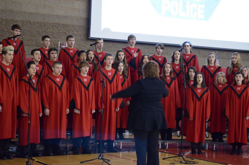 by: PHOTO BY: JAMIE SCHERSCHEL - Oregon City High School's choir, directed by Amy Aamodt, performs at the schoolwide Veterans Day assembly this month.