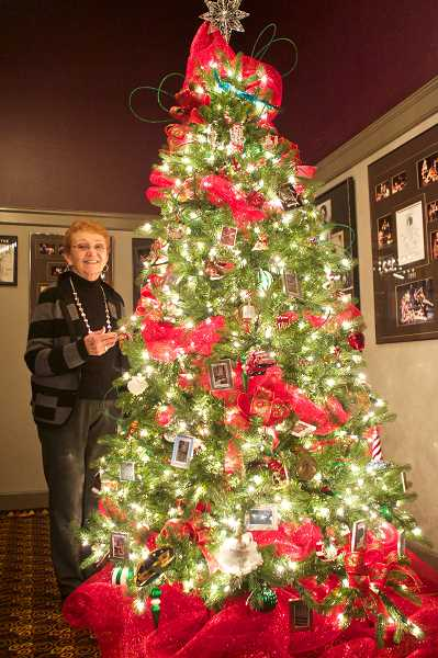 by: STAFF PHOTO: JAIME VALDEZ - Kay Vega, executive producer at Lakewood Center for the Arts, stands by a Christmas tree designed by Margaret Chapman and Jane Reed that will be auctioned at the Lakewood in Lights gala Dec. 2.