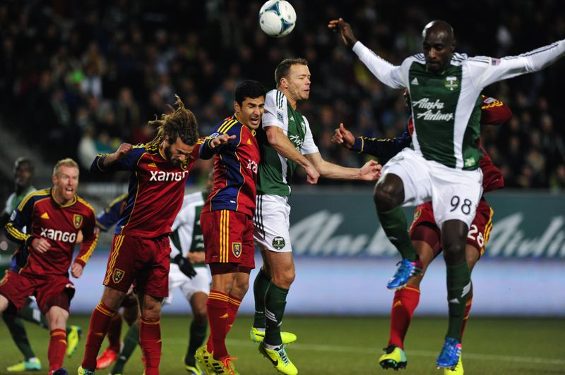 The Timbers push forward early in the game, and Jack Jewsbury (second from right) tries a header off a corner kick as teammate Mamadou 'Futty' Danso (right) goes for the ball as well.