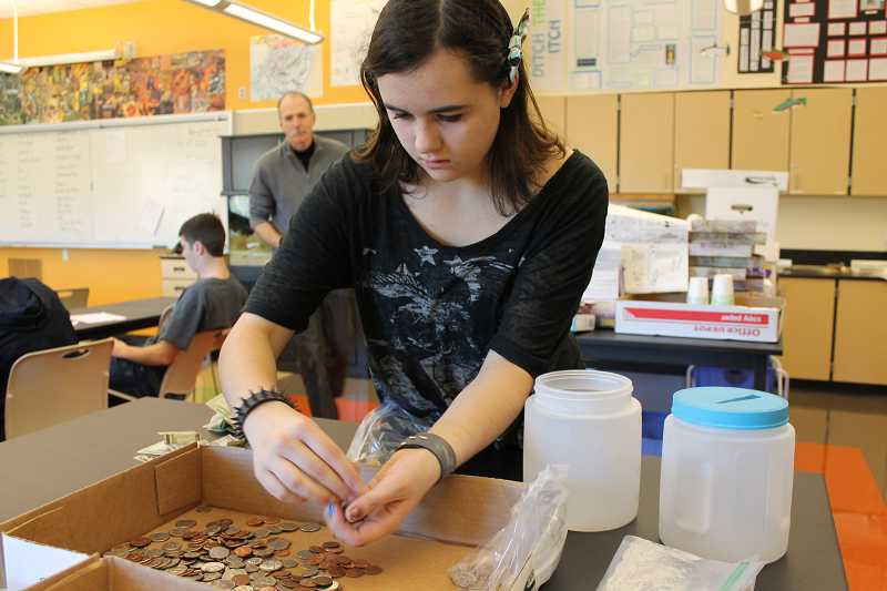 by: SPOKESMAN PHOTO: KATE HOOTS - Megan Howe, a junior at Wilsonville High School, sorts the donations her oceanography class collected Nov. 21 for typhoon relief.