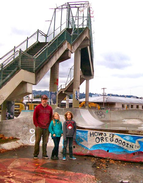 by: RITA A. LEONARD - Colin Sharp, owner of Unheard Skateboard Distribution, stands with his children, India & Kiran, in front of the railroad overcrossing and at the site of the Brooklyn Street Skate Spot, just before both were demolished.