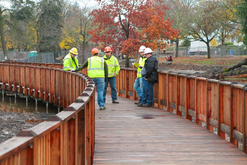 by: DAVID F. ASHTON - Inspectors take notes on finishing touches needed on the curved boardwalk by Crystal Springs Creek in Westmoreland Park.