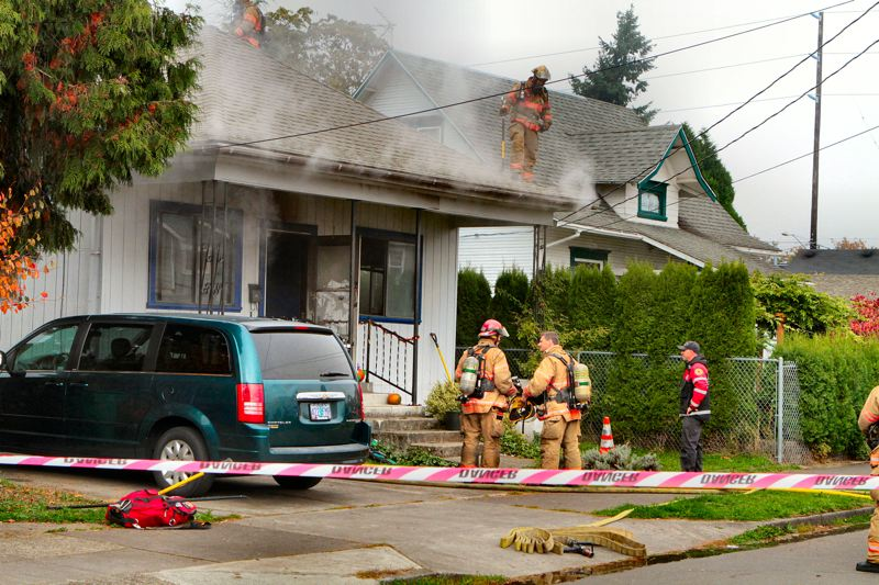 by: DAVID F. ASHTON - Firefighters evaluate the fires progress, as smoke pours from the eves of the house at 4535 S.E. 66th Avenue.