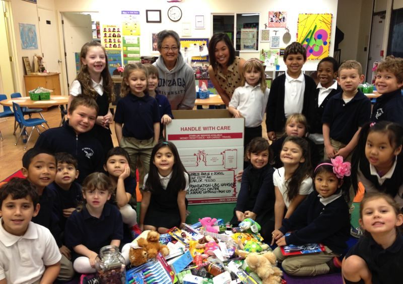 by: CONTRIBUTED PHOTO: JACKIE BROCKA - Kindergarten students at St. Therese School emptied their piggy banks, raising more than $300 and filling boxes of personal items for typhoon relief in the Philippines. The school worked with the company LBC Express.
