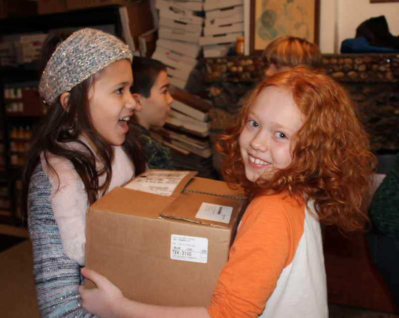 by: TIDINGS PHOTO: KATE HOOTS - Trillium Creek Primary School fourth-graders Ava Reyes, left, and Addison Sobotta work together to carry a heavy box of canned food donations to be weighed at the West Linn Food Pantry on Friday.