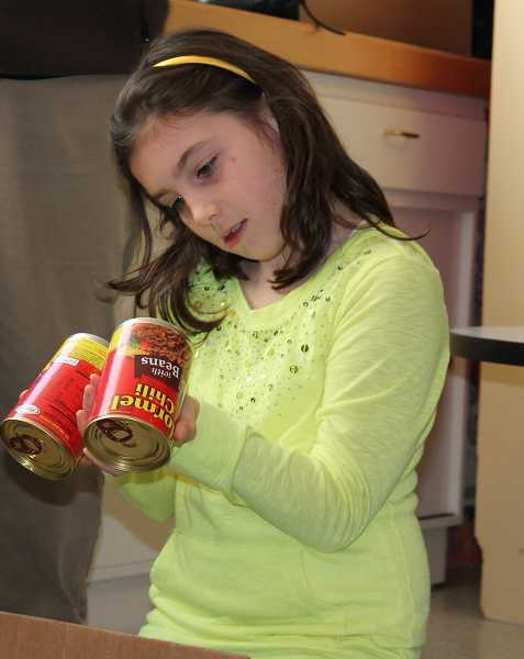 by: TIDINGS PHOTO: KATE HOOTS - Avery Briggs, a fourth-grader at Trillium Creek Primary School, checks the expiration dates on cans of food donated to the West Linn Food Pantry on Friday.