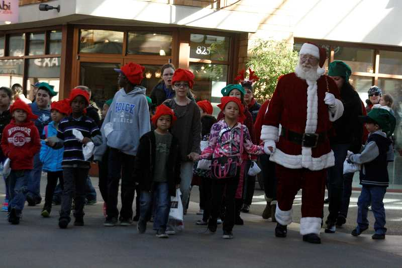 by: PHIL HAWKINS - Santa and his entourage at Woodburn Premium Outlets
