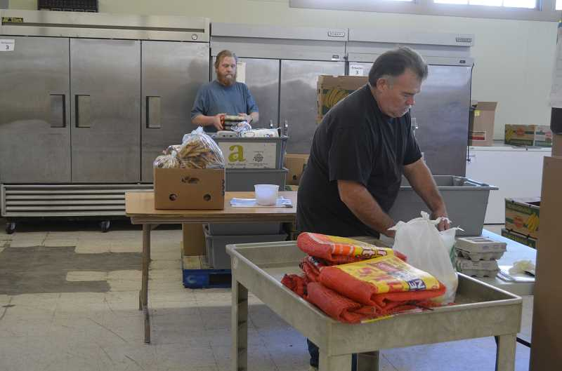by: JANIS BRENTANO - (Foreground) Perri Castor, a new volunteer, and Brandon Rose, a volunteer for the past year, help sort food donations at Woodburn AWARE Food Bank.