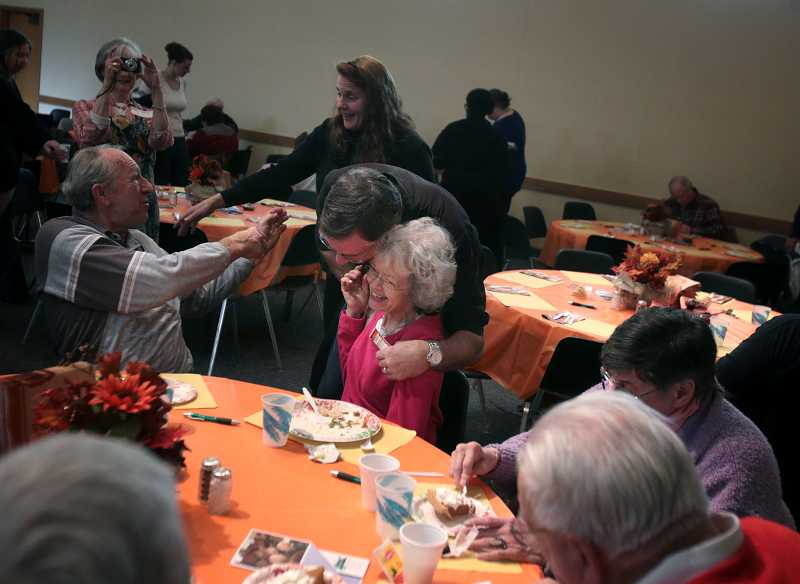 by: JONATHAN HOUSE - Tigard Church of God member Carrie Williams gets a hug from Del Goff during the churchs Saturday pre-Thanksgiving feast. The church is one of several places offering a Thanksgiving meal to people without a place to celebrate.