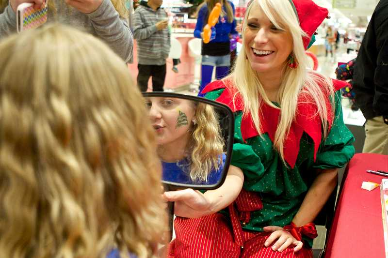 by: TIMES PHOTO: JAIME VALDEZ - Elf Danica Holtan shows 12-year-old Lily Moser her face after painting a Christmas tree on it during Make-A-Wish Oregon's letter-writing kickoff campaign at Macy's department store. The Macy's Believe Campaign donates cash to the organization for every letter written to Santa.