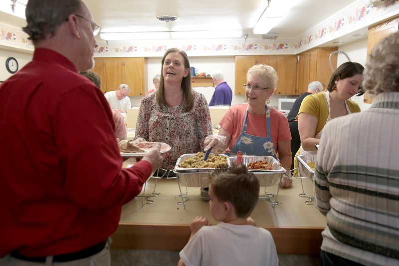 by: JONATHAN HOUSE - Conni Leloff, left, and Linda Dobbins volunteered their time serving food during the Tigard Church of Gods Saturday pre-Thanksgiving feast.