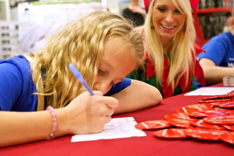 by: TIMES PHOTO: JAIME VALDEZ - Lily Moser writes her letter to Santa as part of Macy's Believe Campaign at the Washington Square mall. The campaign will donate $1 for every letter to Santa dropped off at Macy's department stores across the state.