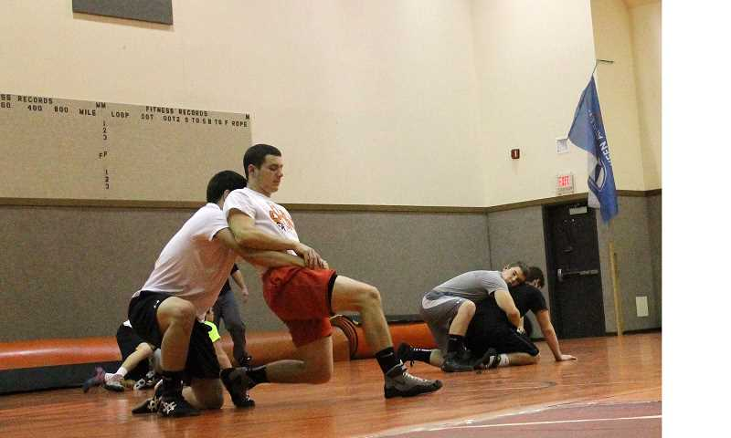 by: CORY MIMMS - Austin Keller, in red, breaks free of his opponent's hold during practice.