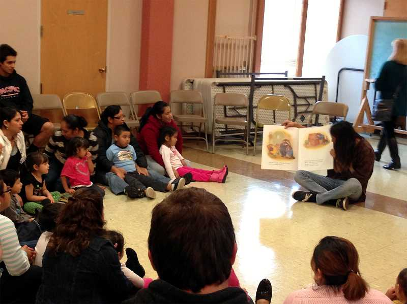 by: COURTESY PHOTO: EMILEE HINGES - Pacific University student Tristen Nolasco read to children in the Adelante Mujeres program at the book donation Monday, Nov. 18, at St. Anthony Catholic Church.