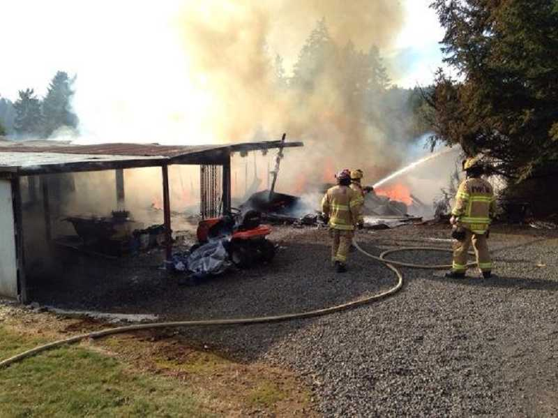 by: TVF&R - Fire crews mop up following a barn fire that destroyed a structure on Edy Road Tuesday.