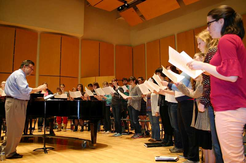 by: PHOTO BY COLLEEN CORNISH - Dr. Scott Tuomi and the Chamber Singers at Pacific University practice for the Dec. 7 Holiday Concert.