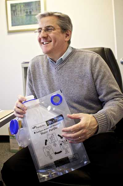 by: TIMES PHOTO: JAIME VALDEZ - Puralytics CEO Mark Owen holds a water purification backpack that is shipped to places around the world that are dealing with natural disasters.