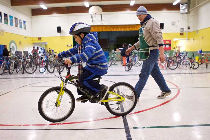 by: TIMES PHOTO: JAIME VALDEZ - Steven Kung, co-founder of Bikes For Humanity PDX, watches as David Ortiz Soto, 6, rides a bike he's interested in at Barnes Elementary School.