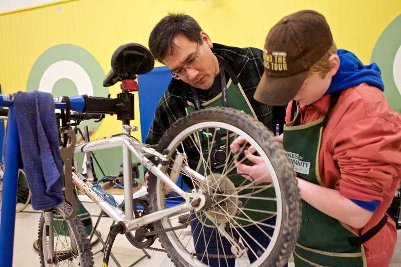 by: TIMES PHOTO: JAIME VALDEZ - Bikes For Humanity PDX volunteers Casey ODonnell and Fionn Anderson, 14, apply chain oil to a bike during an event at Barnes Elementary School.