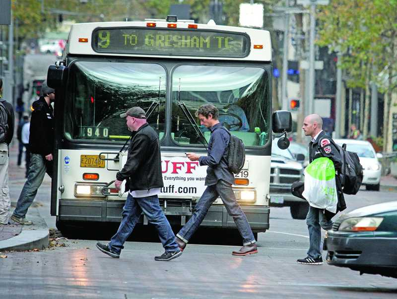 by: TIMES PHOTO: JONATHAN HOUSE - Distracted walking is becoming a big issue for transit agencies like TriMet, which is testing pedestrian warning system on its buses. These pedestrians are crossing the street during evening rush hour at Southwest Fifth Avenue and Taylor Street in downtown Portland.