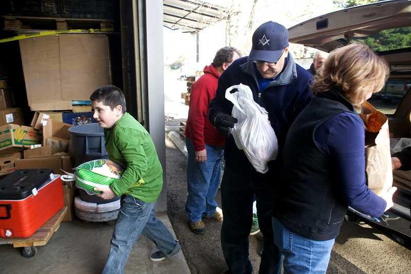 by: TIMES PHOTO: JAIME VALDEZ - Joseph Weiner, 10, helps his father, Garry, unload food donated to the Sunshine Pantry.
